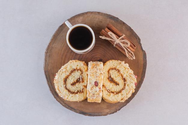 Tasse americano mit kuchenröllchen und zimt auf holzbrett