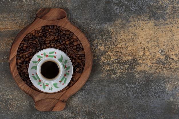 Tasse aroma-espresso mit kaffeebohnen auf holzbrett.