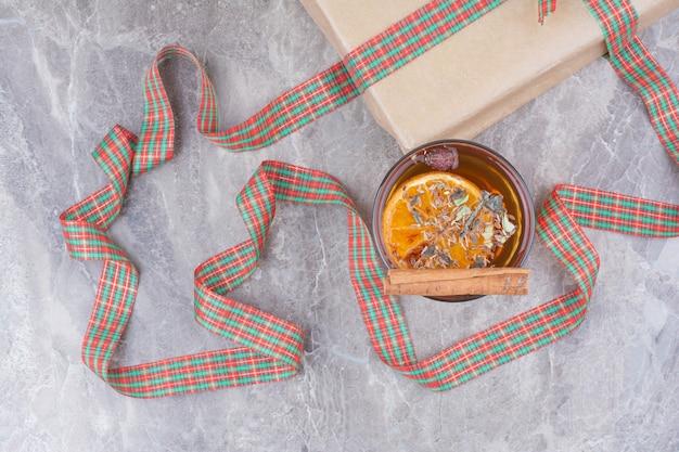 Tasse aroma-tee mit geschenk und bogen auf marmor-backgrond.