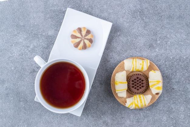 Tasse aromatee mit verschiedenen keksen auf marmoroberfläche