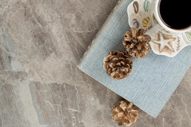 Tasse aromatischen kaffee auf buch mit tannenzapfen