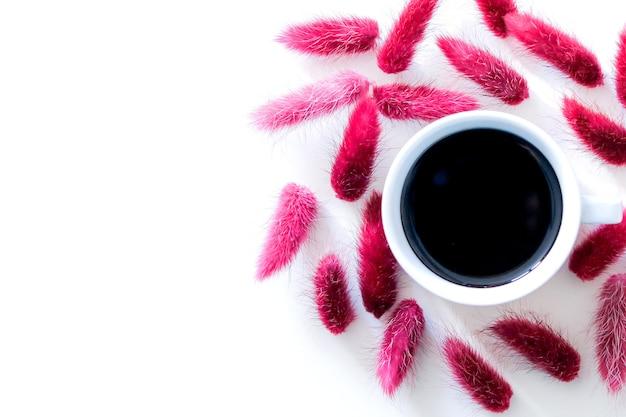 Tasse aromatischen schwarzen espressokaffee lokalisiert auf weißem hintergrund, umgeben von einem satz trockener rosa herbstblumen