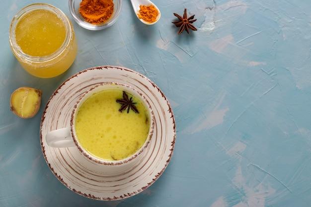 Tasse ayurvedische goldene kurkuma-latte-milch mit kurkumapulver, zimt, ingwer und anisstern auf hellblauem hintergrund, draufsicht, kopienraum