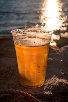 Tasse bier auf dem hintergrund des ozeans während des sonnenuntergangs