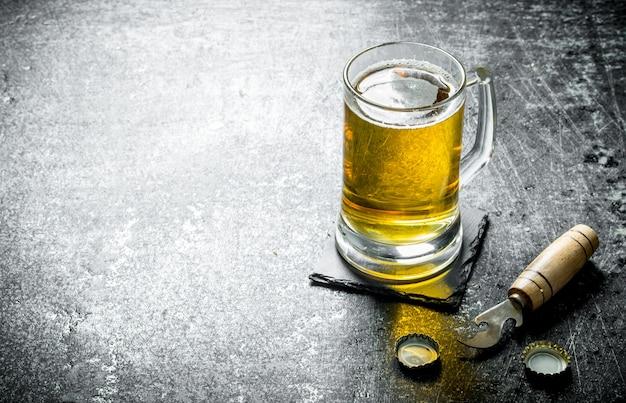 Tasse bier auf einem schwarzen ständer mit öffner. auf schwarzem rustikalem tisch