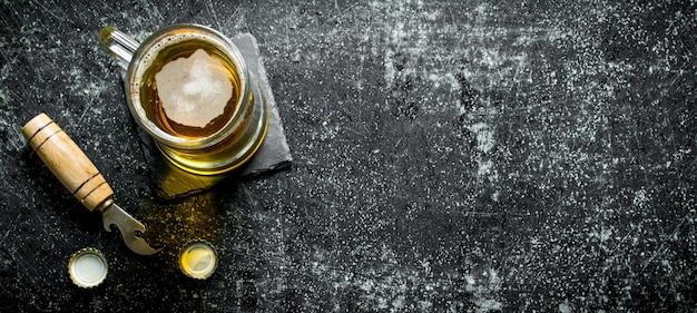 Tasse bier auf einem schwarzen ständer mit öffner. auf schwarzer rustikaler oberfläche