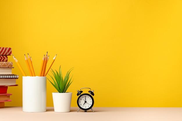 Tasse bleistifte und notizblöcke auf dem schreibtisch gegen gelb