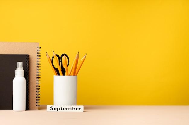 Tasse bleistifte und notizblöcke auf schreibtisch gegen gelbe hintergrundvorderansicht