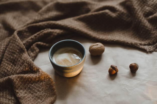 Tasse cappuccino auf braunem papierstrukturhintergrund mit gemütlichen warmen karierten walnüssen und eicheln