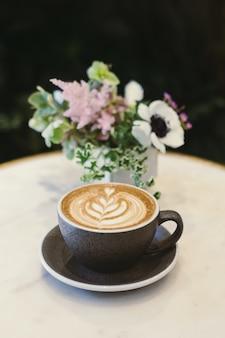 Tasse cappuccino auf untertasse neben blumenmittelstück