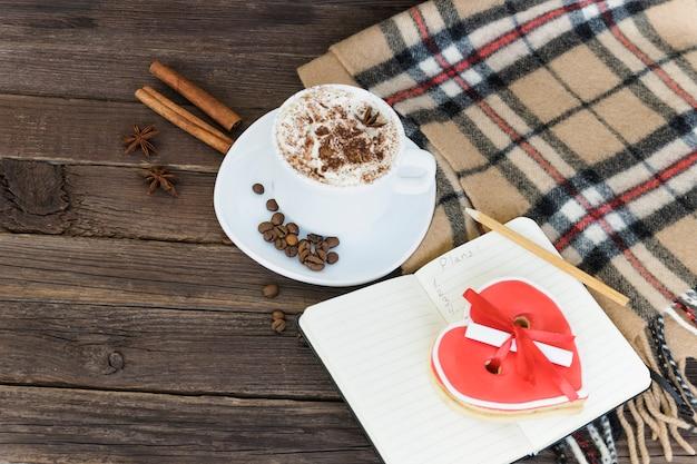 Tasse cappuccino, herzförmige kekse breite nachricht, notizbuch und kariertes plaid auf einem braunen holztisch