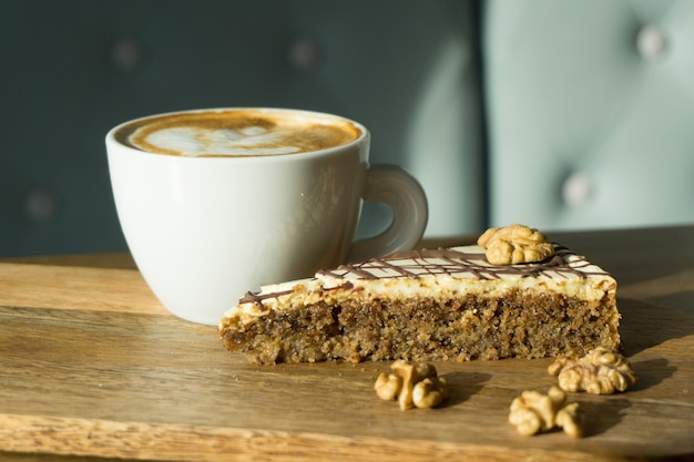 Tasse cappuccino mit einem stück kuchen
