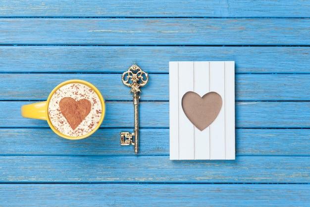 Tasse cappuccino mit herzformsymbol, schlüssel und fotorahmen auf blauem holz.