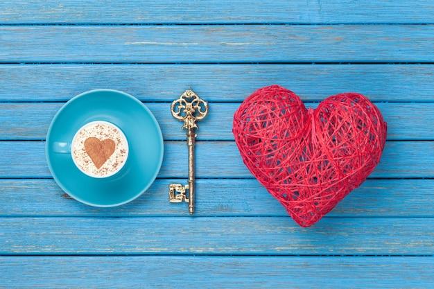 Tasse cappuccino mit herzformsymbol, schlüssel und spielzeug auf blauem holz.
