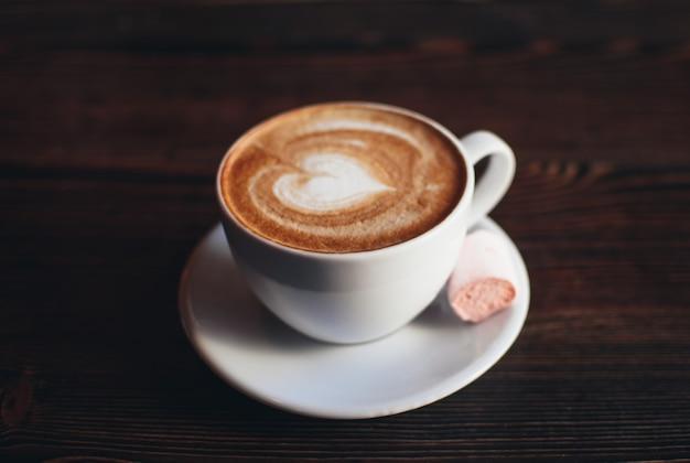 Tasse cappuccino mit marshmallow auf einem hölzernen hintergrund.