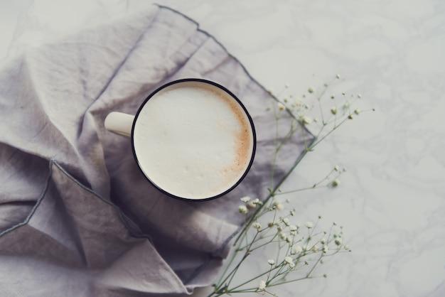 Tasse cappuccino mit tannenzweigen und blumenbabyatem