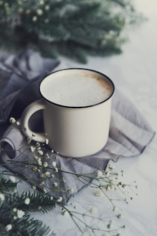 Tasse cappuccino mit tannenzweigen und gypsophila-blüten