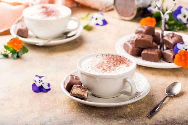 Tasse cappuccino mit weichen nougatschokoladenbonbons