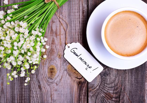 Tasse cappuccino und ein bouquet von weißen maiglöckchen