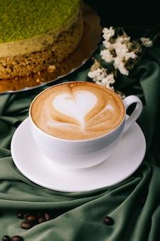 Tasse cappuccino und kuchen auf dem tisch