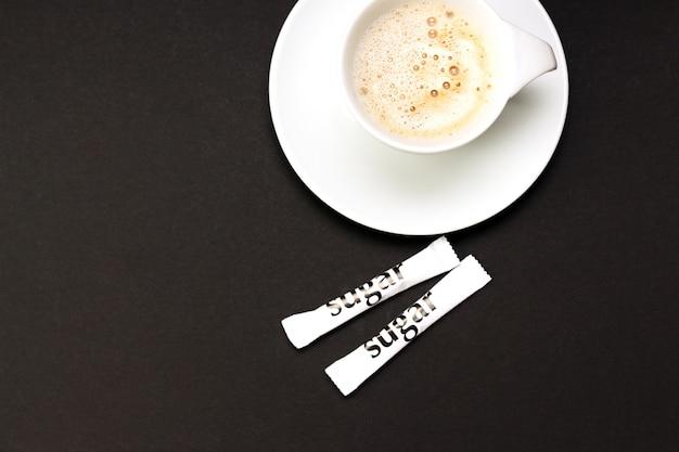 Tasse cappucino-kaffee mit weißen zuckerbeuteln auf schwarzem tisch.