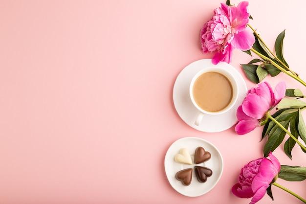 Tasse cioffee mit pralinen, rosa pfingstrosenblüten auf rosafarbenem pastellhintergrund. ansicht von oben,
