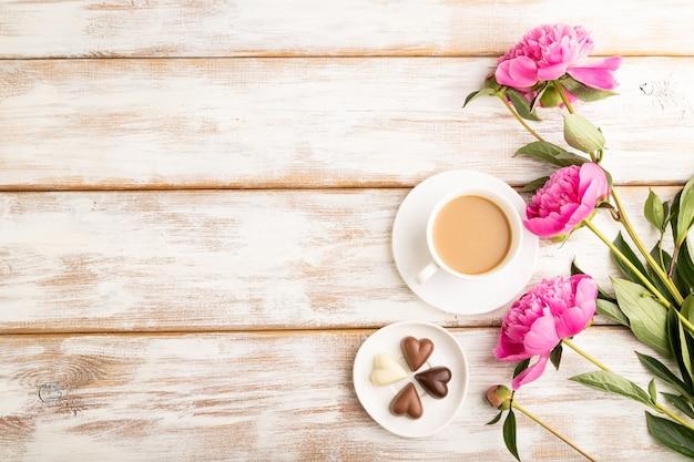 Tasse cioffee mit pralinen, rosa pfingstrosenblüten auf weißem holzhintergrund. ansicht von oben,