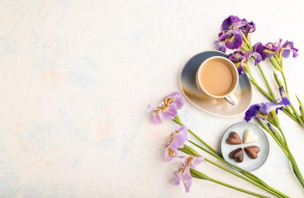 Tasse cioffee mit pralinen und lila irisblumen auf weißem betonhintergrund. ansicht von oben,
