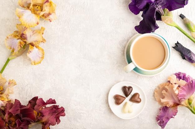 Tasse cioffee mit pralinen und lila und burgunderroten irisblumen auf grauem hintergrund.