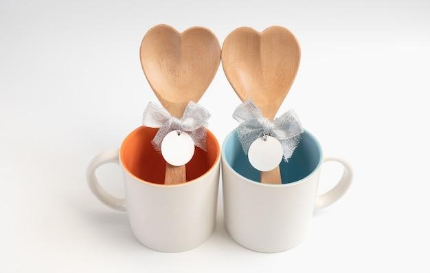 Tasse der liebe, zwei kaffeetassen mit holzlöffel in herzform auf weißem hintergrund