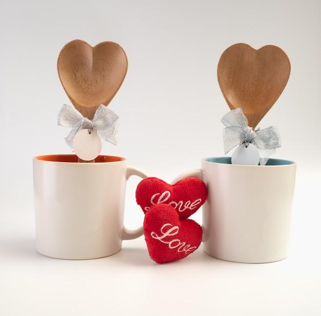 Tasse der liebe, zwei kaffeetassen mit roter herzikone und holzlöffel auf weißem hintergrund