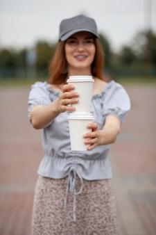 Tasse des weißen papiers zwei mit kaffee in der frauenhand. zeit zum kaffeetrinken in der stadt. kaffee zum mitnehmen. genießen sie den moment, machen sie eine pause. einweg-pappbecher nahaufnahme. leckeres heißgetränk. leerzeichen für text,
