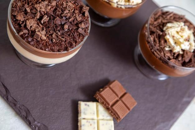 Tasse dessert mit milchschokoladenmousse mit weißen schokoladenspänen