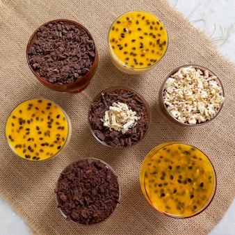 Tasse dessert mit milchschokoladenmousse und weißen schokoladenspänen, ganache-mousse und passionsfruchtmousse.