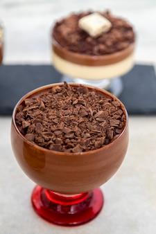 Tasse dessert mit milchschokoladenmousse und weißen schokoladenspänen und ganache-mousse.