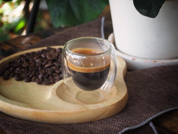 Tasse espresso auf dem tisch. becherglas für shot-cocktail oder kaffeegetränke. nahaufnahme von einem glas espresso. heißer kaffee in einem glas mit doppelwänden isoliert auf weißem hintergrund.
