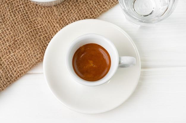 Tasse espresso mit glas wasser auf weißem tisch