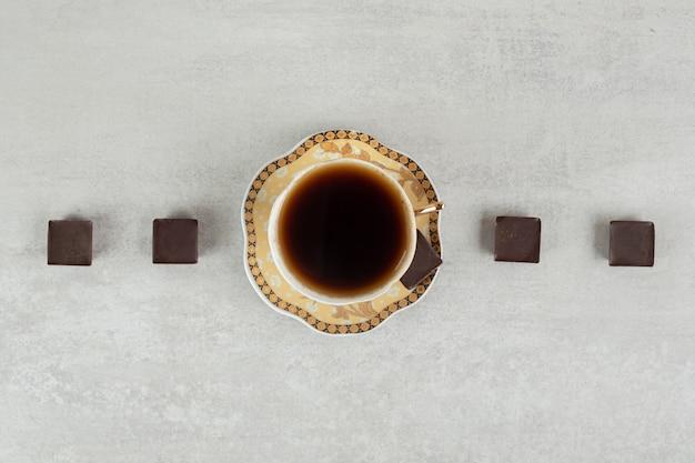 Tasse espresso mit schokoladenstückchen auf marmoroberfläche