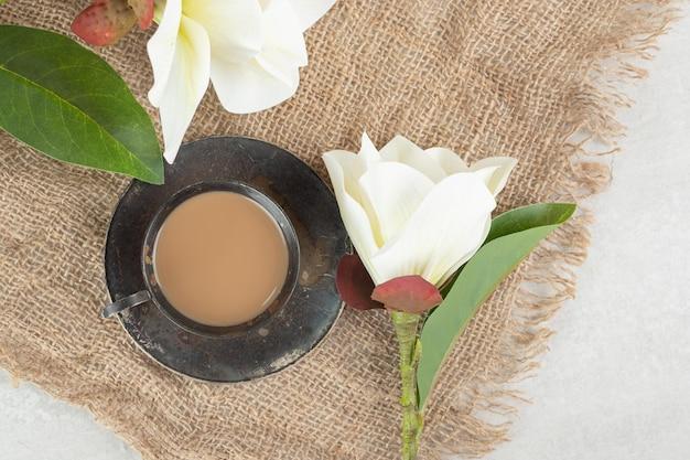Tasse espresso und weiße blumen auf sackleinen.