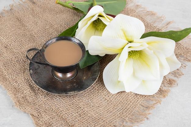 Tasse espresso und weiße blumen auf sackleinen