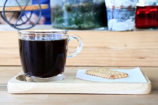 Tasse espressokaffee mit crackerplätzchen auf holzteller in der morgenzeit.