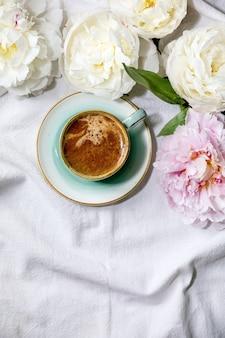 Tasse espressokaffee, rosa und weiße pfingstrosenblumen mit blättern. flache lage, kopierraum