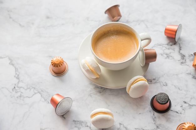 Tasse espressokaffee serviert mit makronen und kapseln auf marmortisch.
