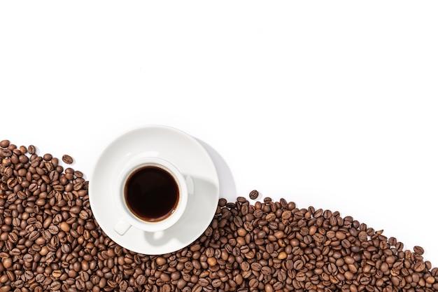 Tasse espressokaffee und geröstete bohnen auf weiß isoliert. speicherplatz kopieren. draufsicht