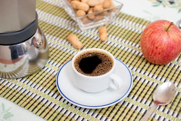 Tasse expresso-kaffee mit erdnüssen und obst