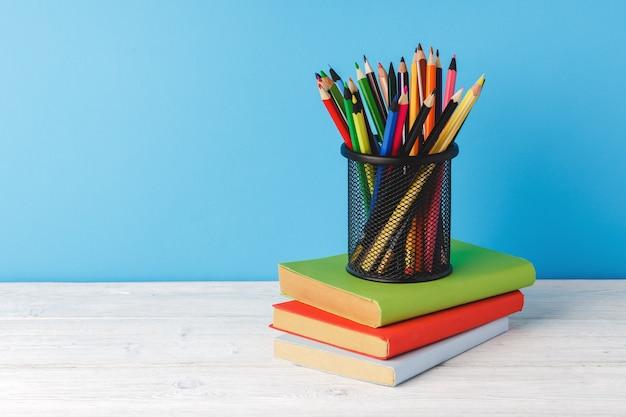 Tasse farbstifte und stapel bücher auf tisch