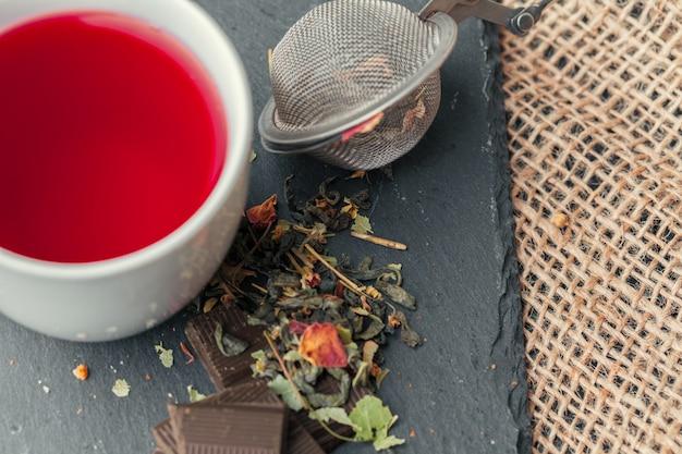 Tasse frisch gebrautes obst und kräutertee, dunkle stimmung. teezeremonie