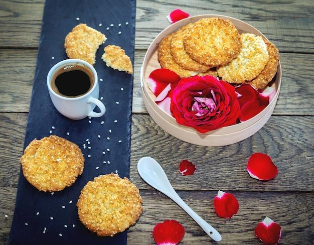 Tasse frisch gebrühten espressokaffee, sesamplätzchen und rote rosenblume in einer holzkiste