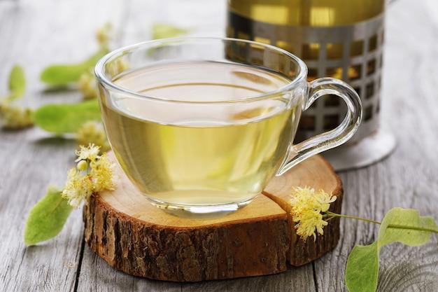 Tasse frischen tee aus lindenblättern auf einem holzständer