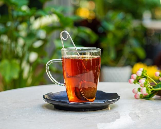 Tasse frischer aromatischer tee auf dem tisch mit naturblumenoberfläche